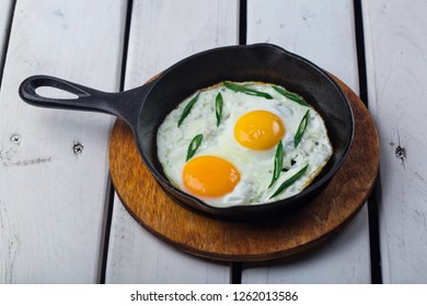 Fried eggs for delicious healthy easy breakfast on a table. Fresh homemade meal on a frying pan. Internetional breakfast.