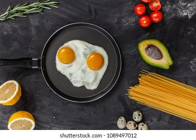 Fried eggs with different food ingredients on the black table, top view