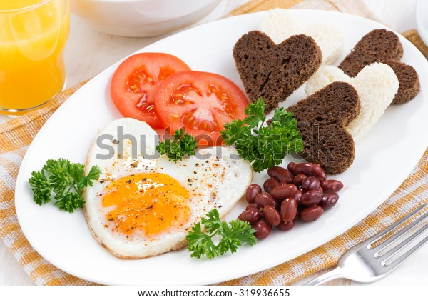 fried eggs in the form of heart for breakfast Valentine's Day on white plate, close-up, horizontal