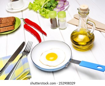 Fried eggs in a frying pan with fennel, tablewares, orange juice in a glass and chilli.