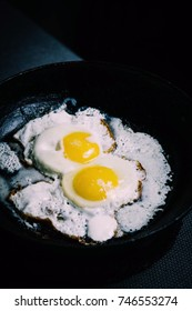 fried eggs in a frying pan under sour cream sauce, two pieces, against a dark background