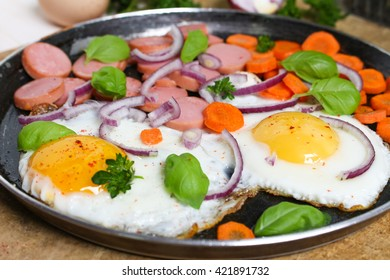 Fried eggs in a frying pan with vegetables , greens and crispy bread