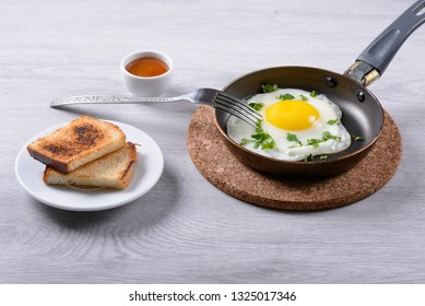fried eggs on a frying pan, toast and sauce