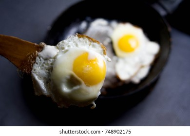 fried eggs on a frying pan. The egg is picked up by a wooden spatula. Flip over