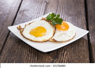 Fried Eggs on a plate (wooden background)