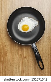 Fried eggs. Pan with handle on wood background