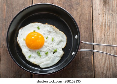 Fried eggs in pan with handle on table, top view