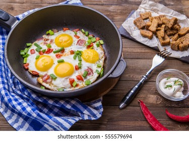 Fried eggs in pan with tomatoes and green fresh onion. Breakfast. Healthy food.