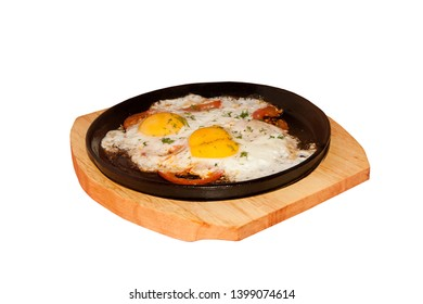 fried eggs roasted with tomatoes on the frying pan standing on a wooden support, isolation. White background