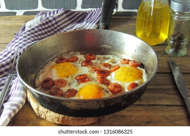 Fried eggs with sausage and tomatoes in frying pan served with salad on dark rustic background. Top view.