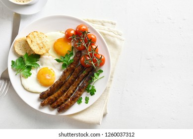 Fried eggs, sausages and cherry tomatoes on plate over white stone background with copy space. Dish for breakfast. Top view