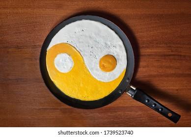 fried eggs in the shape of yin yang in a pan
