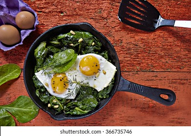 Fried eggs with spinach and pine nuts on iron skillet