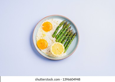 Fried eggs with steamed asparagus flat lay on blue gray background. Delicious healthy lunch. Keto diet