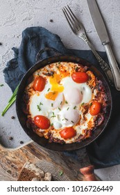 fried eggs with tomato and mushrooms in a frying pan on a concrete surface. Shakshuka