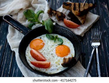 Fried eggs with vegetables and toasts