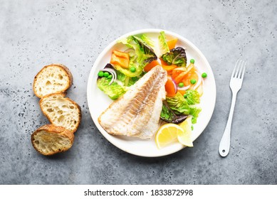 Fried fillet of sea white cod fish with juicy lettuce, capsicum, lemon, green peas on a large white dish on a gray background. Healthy balanced food. Top view