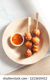 Fried fish balls on a wooden stick, placed on a wooden plate. It is an asian traditional food, can be spicy or sweet. Top and clean view for a homemade dish.