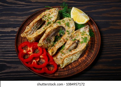 Fried fish in clay plate, on dark wooden background.