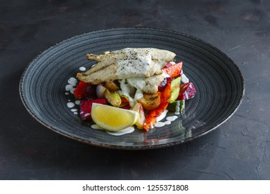 Fried fish fillet with grilled beetroot, carrot, bell pepper, zucchini, garlic on dark background