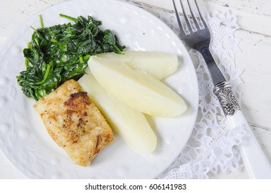 Fried fish fillet with potato and spinach