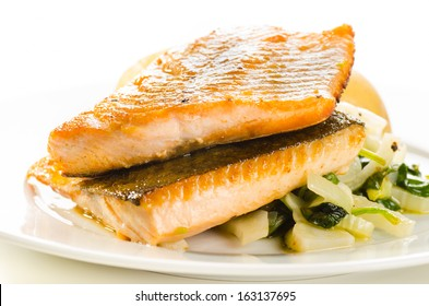 Fried fish fillets with vegetable garnish on white