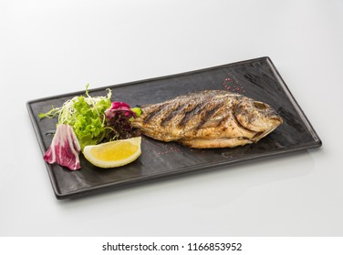Fried fish with lemon and lettuce on a plate isolated on white background.