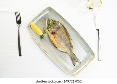 fried fish with lemon and rosemary on a plate