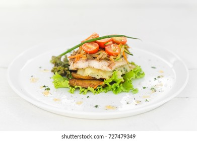Fried fish with mash potato, grilled potato and salad on the white background