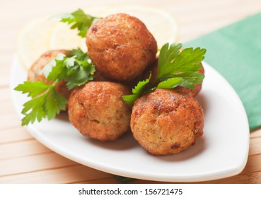 Fried fish meatballs with lemon and parsley