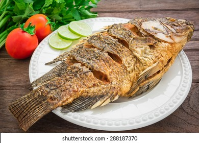 Fried fish on plate with vegetables
