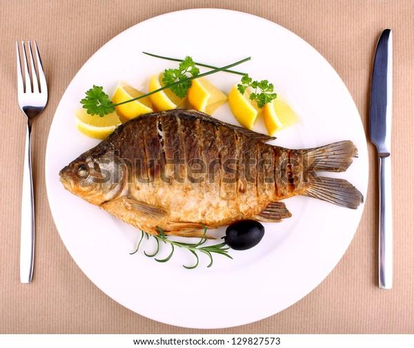 Жареная рыба на белой тарелке с вилкой и ножом, крупным планом