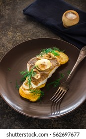 Fried fish with potato and onion on brown plate.Stone background Selective focus.