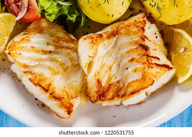 Fried fish with potatoes on wooden table