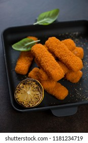 Fried fish sticks or breaded fish fillet in a cast-iron pan, close-up, selective focus