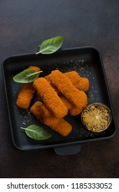 Fried fish sticks or breaded fish fillet in a cast-iron serving pan, studio shot