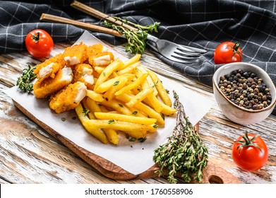 Fried Fish Sticks with French Fries. British fish and chips, fried potato. White wooden background. Top view