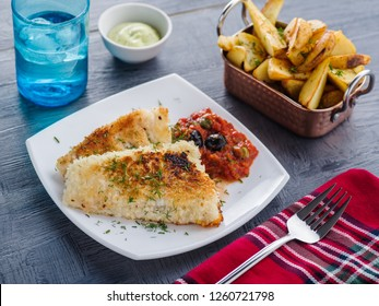Fried fish with tomato-olive sauce and potatoes