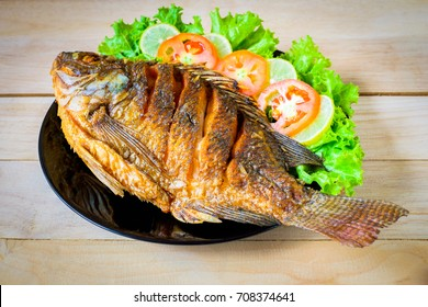 fried fish with vegetable on black dish
