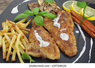fried fish with vegetables on black stone