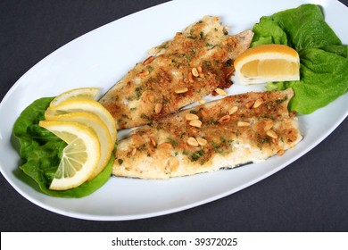 fried fish in white plate over gray
