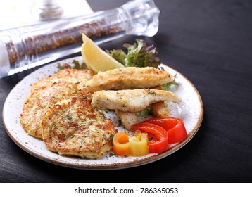 Fried fish with zuccini pancakes on a plate