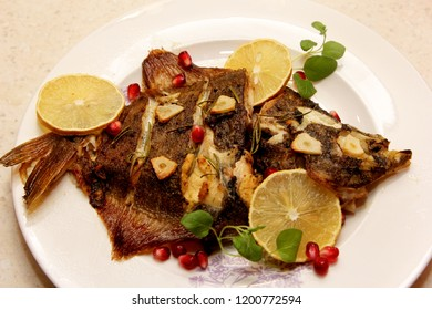 Fried flatfish, flounder served on a plate, with lemon, herbs and garlic