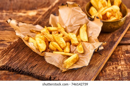 fried French fries on a paper on the wooden table. Crisp golden deep fried french fries; hot potatoes frying and ready to be eaten... yum!
