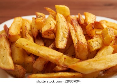 fried French fries on a plate on the wooden table