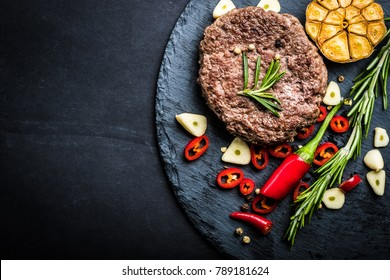 Fried fresh large beef burger with herbs and garlic on black slate, top view, space for text