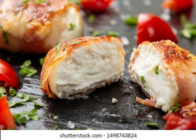 Fried goat cheese covered with smoked bacon - close up view