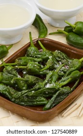 Fried green peppers in salt. Pimientos del Padron. White background. Spanish Cuisine. Ribeiro wine in foreground.