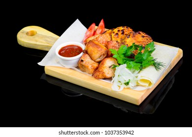 Fried grilled meats with vegetables on a black background