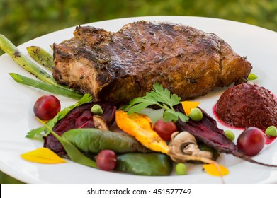 Fried Grilled pork steak on the bone with vegetables, mashed beetroot and berry sauce. Against the background of foliage. Close-up